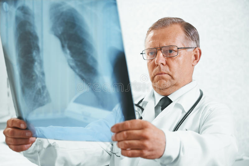 Older doctor examines x-ray image of lungs. Older man doctor examines x-ray image of lungs in a clinic stock images
