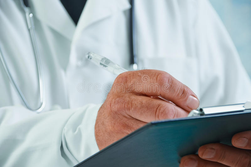 Older doctor writes medical records. Unrecognizable older man doctor writes medical records on clipboard stock photos