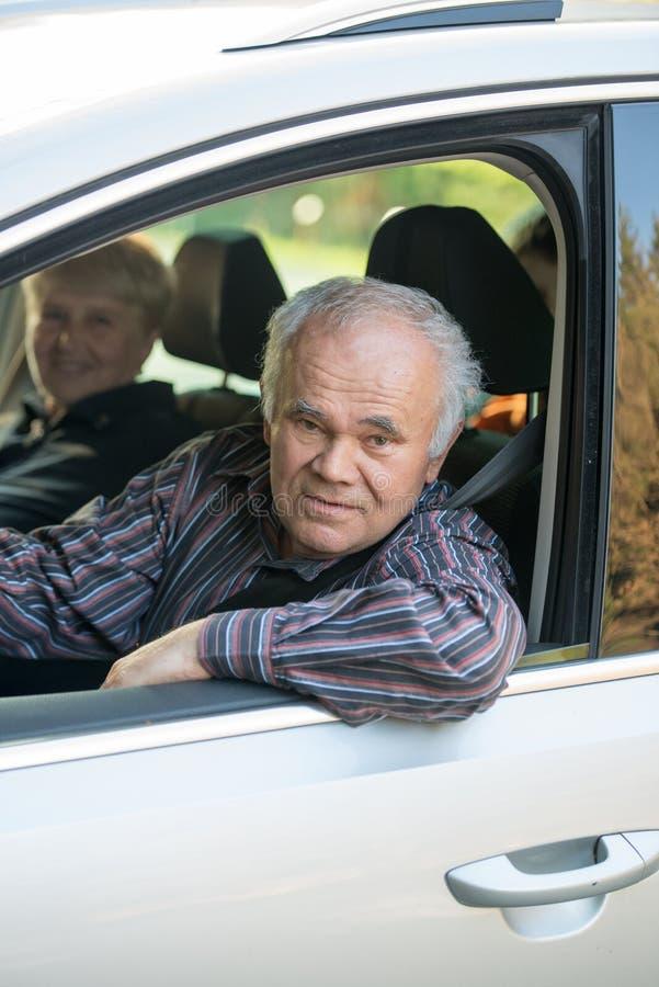 Older driver. Senior men driving a car, senior female passenger sitting in the car royalty free stock photos