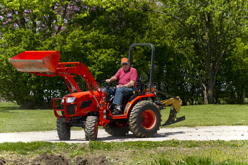 Older Farmer Getting Ready To Plow His Garden. A older farmer getting ready to plow his garden on his compact 4x4 tractor royalty free stock photography