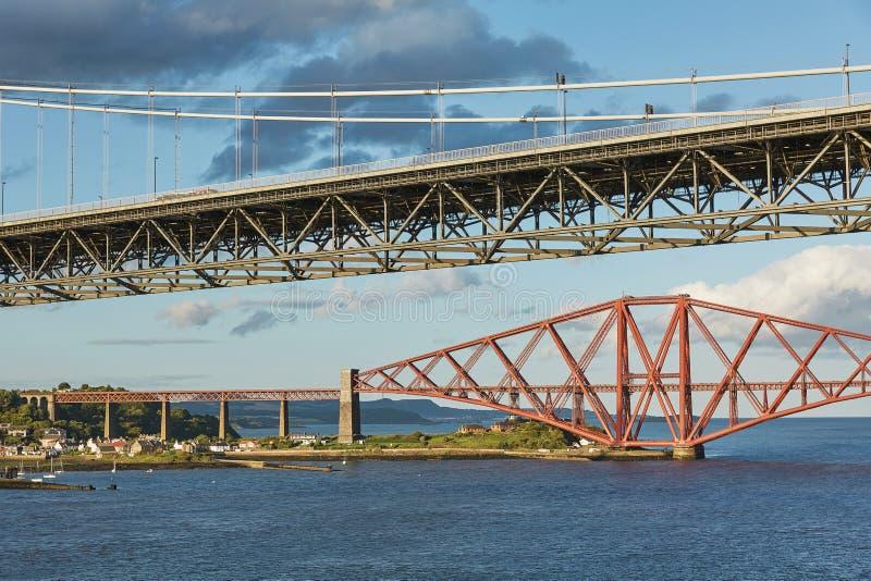Older Forth Road bridge and the iconic Forth Rail Bridge in Edinburgh Scotland.  stock image