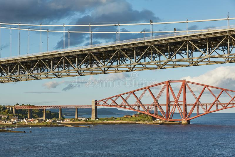 Older Forth Road bridge and the iconic Forth Rail Bridge in Edinburgh Scotland.  royalty free stock photography