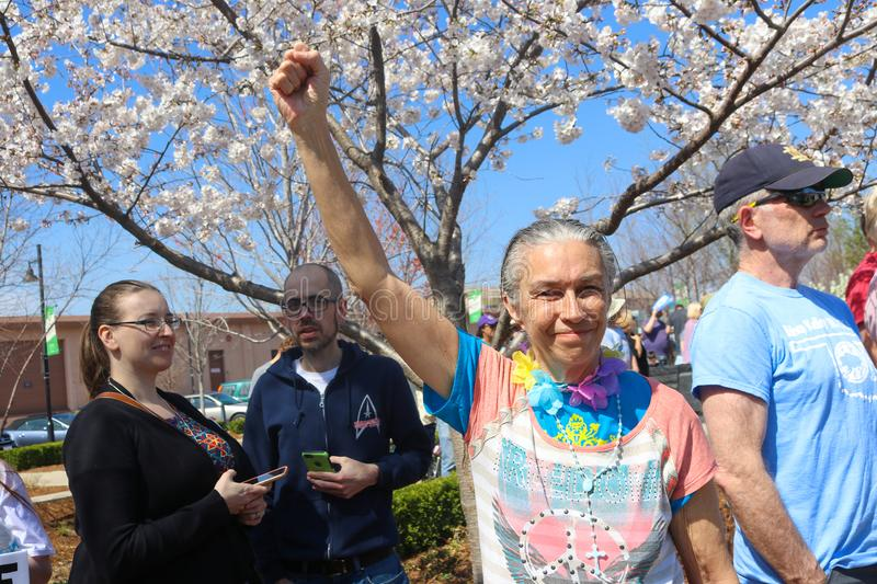 Older grey haired lady with colorful peace sign tee shirt and determined smile and her fist raised in the air at Mark for Life pro royalty free stock photography