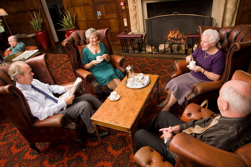 Older group of friends by fireplace stock photos