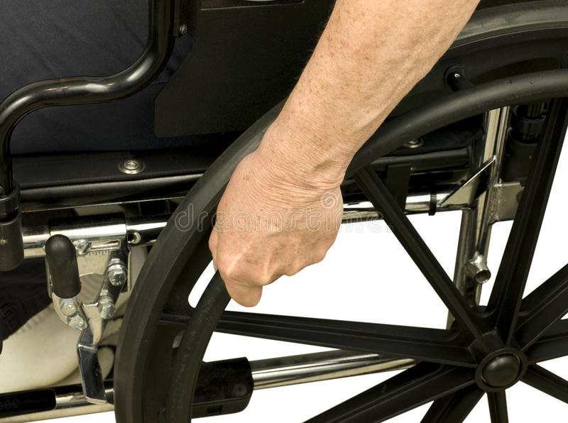 Older hand on wheel chair. Pushing stock images