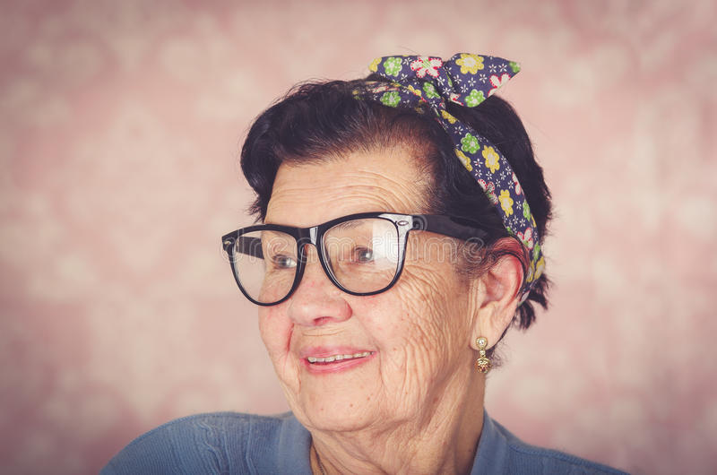 Older hispanic cute woman with flower pattern bow on her head wearing blue sweater and black large framed glasses stock image