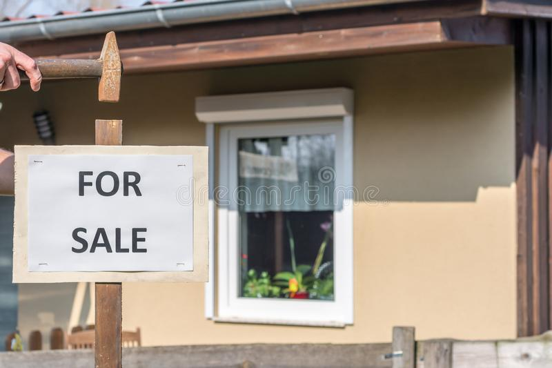 Older house with the sign `For Sale` as a sign of sale. A wooden sign with the inscription `for sale` is hewn on a mast in the ground stock photo