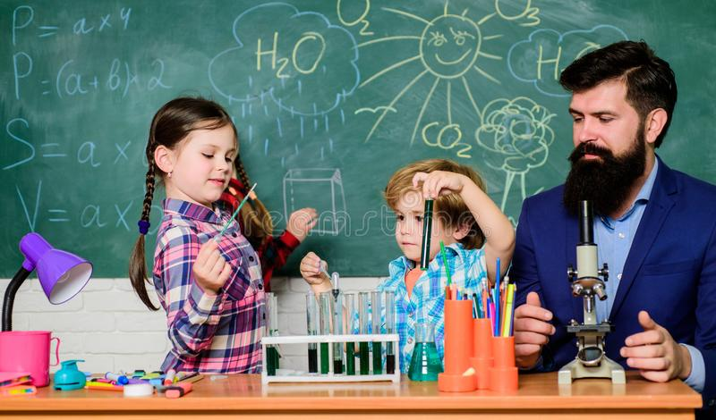 Older kids help younger. School club education. Chemistry themed club. Discover and explore properties of substances royalty free stock photography
