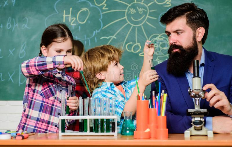 Older kids help younger. School club education. Teacher and pupils test tubes in classroom. Chemistry themed club stock image