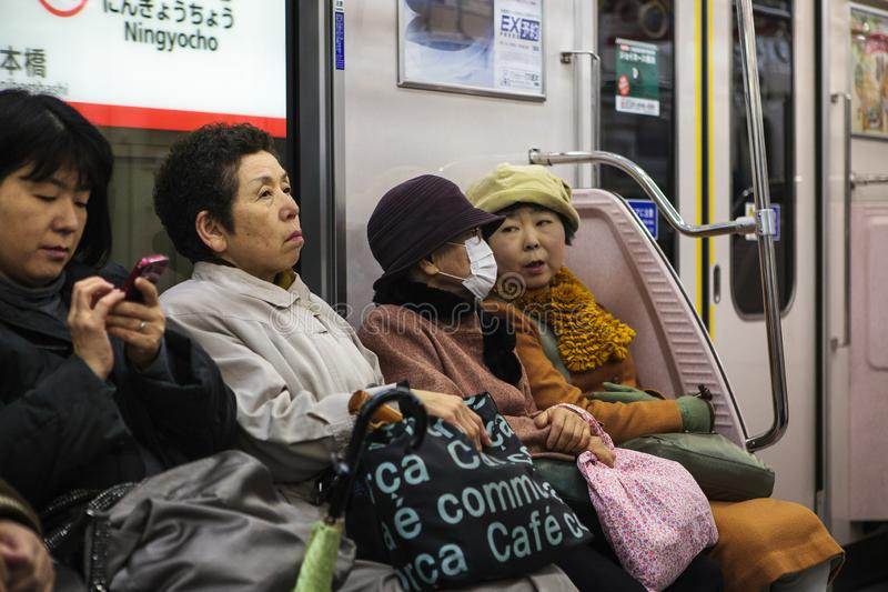 Older ladies taking the subway. Tokyo, Japan - November 25, 2012 :  The subway system in Tokyo is extremely large and everybody uses it, from young to old stock photo