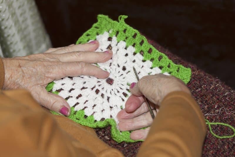 An older lady doing crochet stock photo