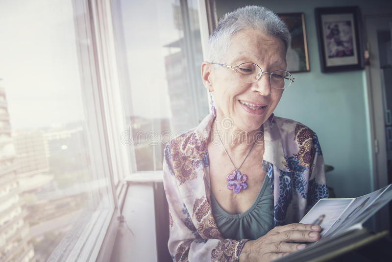 Older lady looking through photographs royalty free stock photos