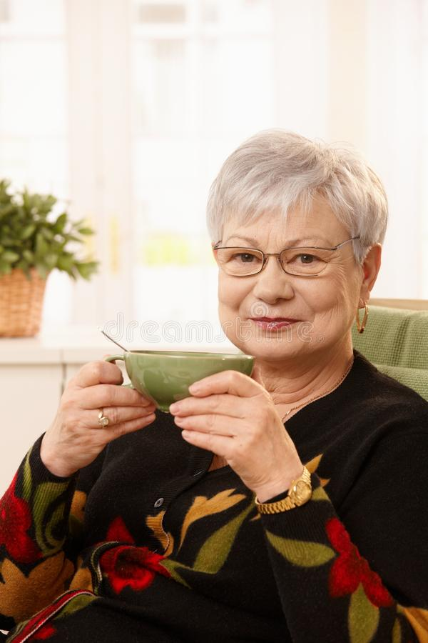 Older lady with tea cup. Older lady sitting at home with tea cup, smiling at camera stock images
