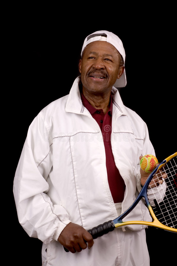 Older male african american tennis player. In white sports outfit over black background stock photography