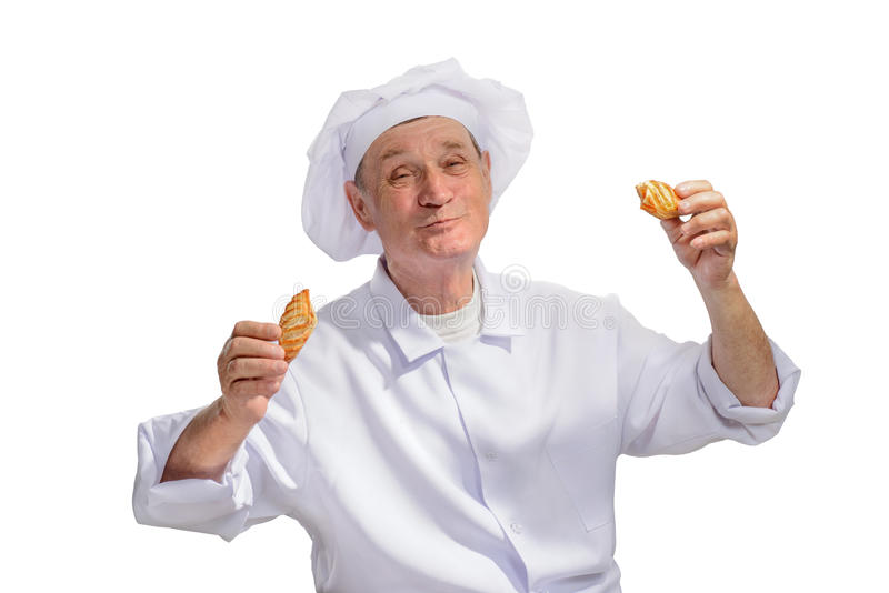 An older man in a cap cook with cakes royalty free stock photography