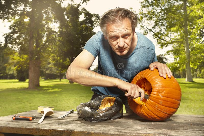 Aging man in city park preparing funny helloween pumpkin royalty free stock image