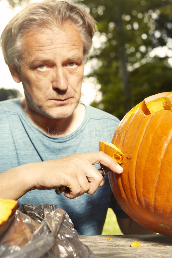 Aging man in city park preparing funny helloween pumpkin royalty free stock photo