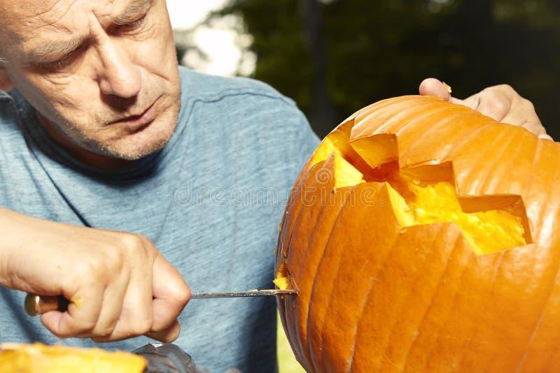 Aging man in city park preparing funny helloween pumpkin stock image