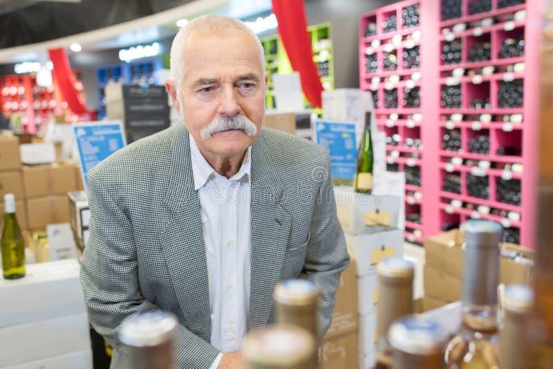 Older man choosing wine at supermarket stock images