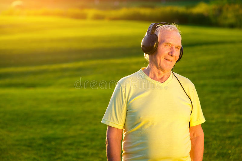 Older man with headphones. Person on green meadow background. My favorite radio station. Re-listen the classics stock image