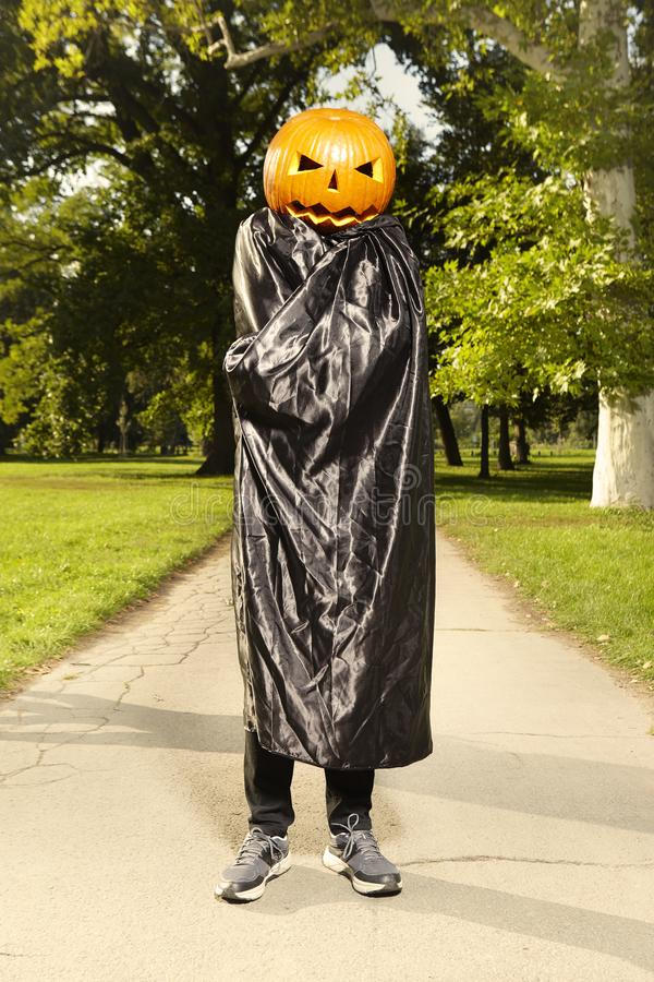 Aging man in city park haunts with pumpkin head. Older man in hooded cloak haunts in city park royalty free stock photography