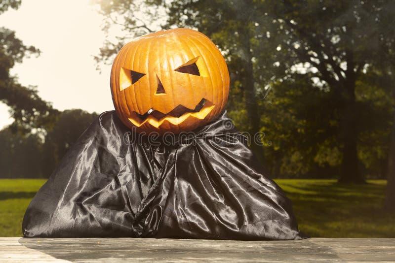 Aging man in city park haunts with pumpkin head. Older man in hooded cloak haunts in city park stock photo