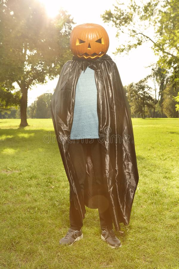 Aging man in city park haunts with pumpkin head. Older man in hooded cloak haunts in city park royalty free stock images