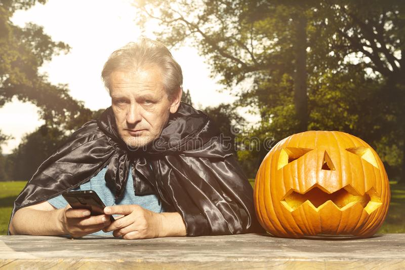 Aging man in city park haunts with pumpkin head. Older man in hooded cloak haunts in city park royalty free stock photos