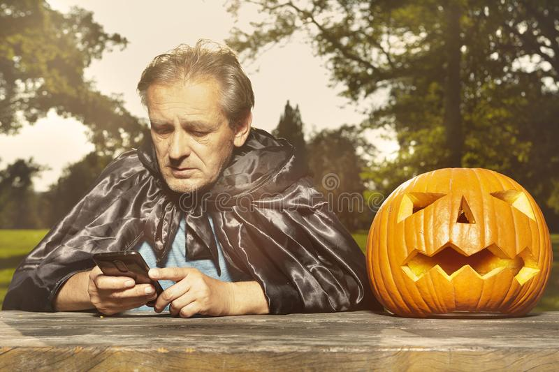 Aging man in city park haunts with pumpkin head. Older man in hooded cloak haunts in city park royalty free stock image
