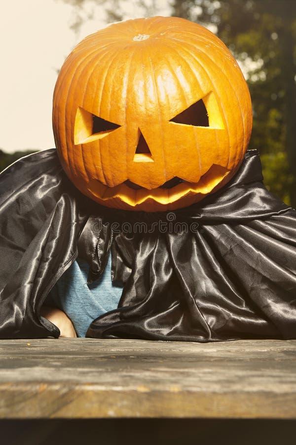 Aging man in city park haunts with pumpkin head. Older man in hooded cloak haunts in city park stock photos
