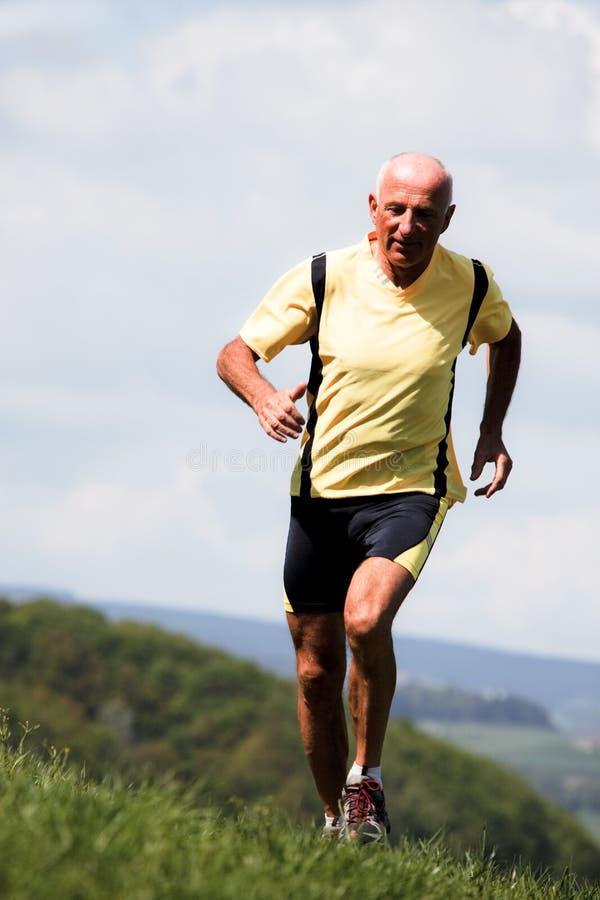 Older man jogging running on meadow stock photo