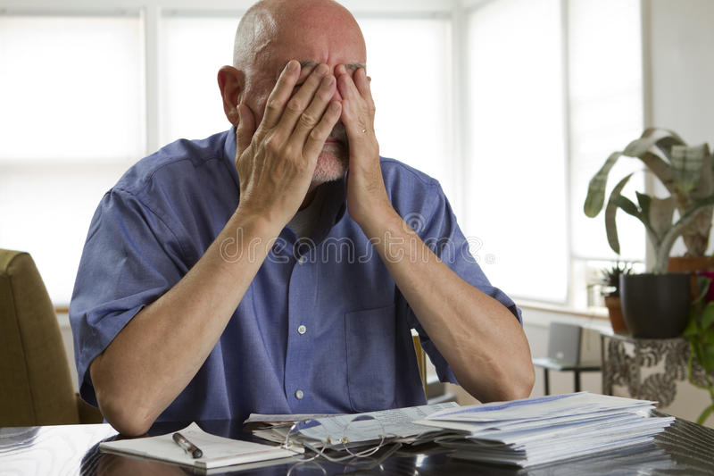 Older man paying bills royalty free stock photo