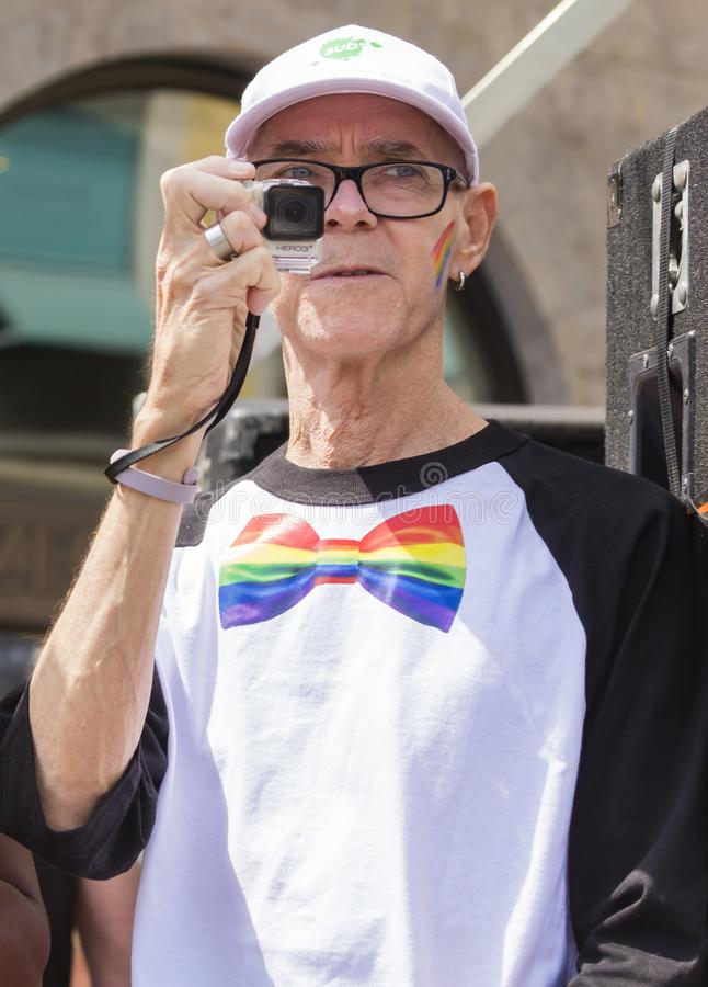 2018: An older man photographing  the Gay Pride parade also known as Christopher Street Day CSD in Munich, Germany.  royalty free stock image