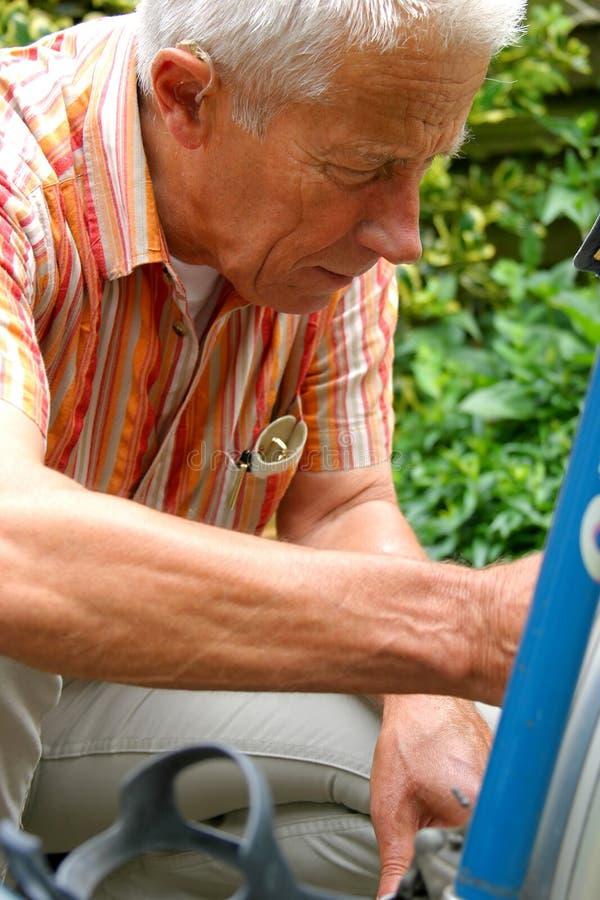 Older man repairing his bike royalty free stock photos