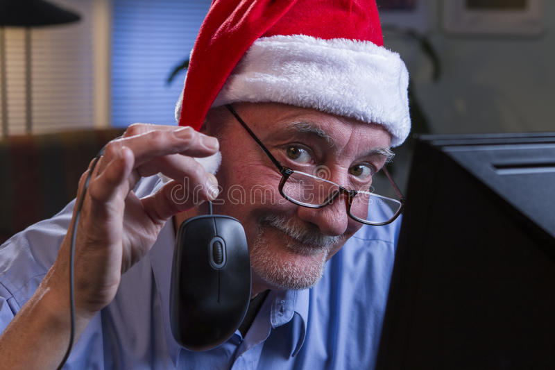 Older man in Santa hat shopping online, horizontal. Older man in Christmas hat Christmas shopping online and holding up computer mouse stock image