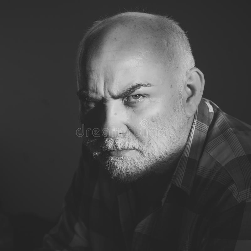 Older man with a serious look. Man with grey beard, frown brows on serious face stock photography