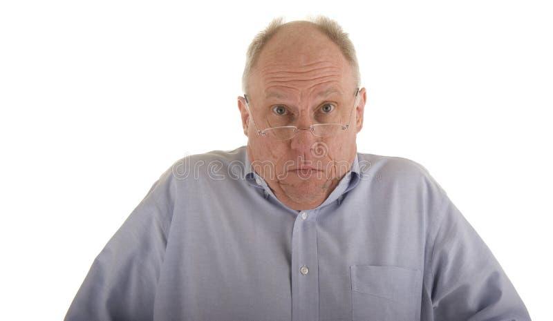 Older Man Shrugging. An older guy in a blue shirt and glasses shrugging his shoulders stock images
