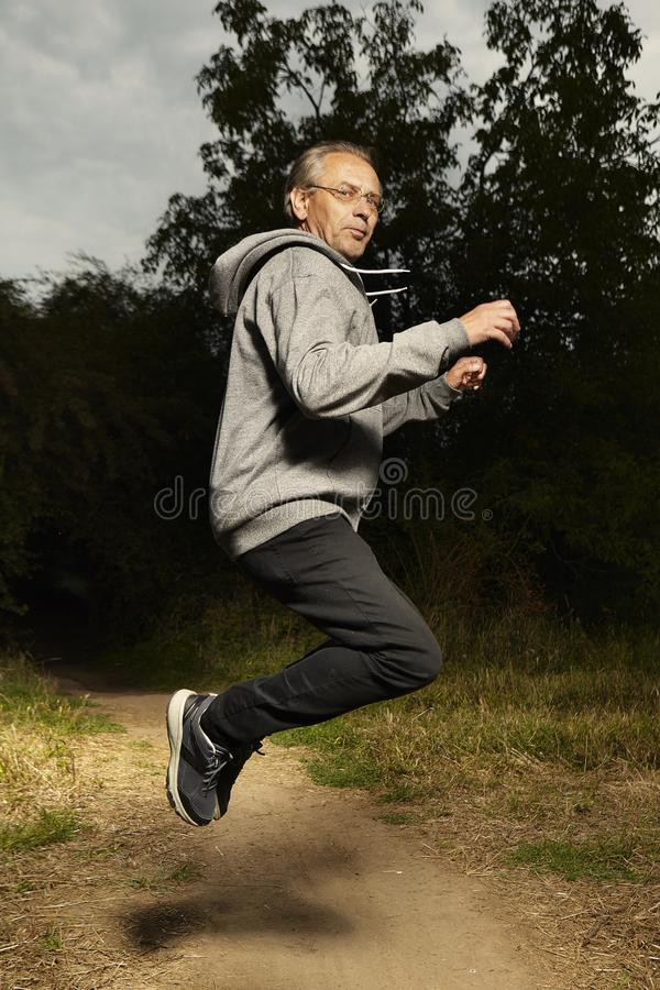 Aging man in hooded shirt jumping on field way royalty free stock image