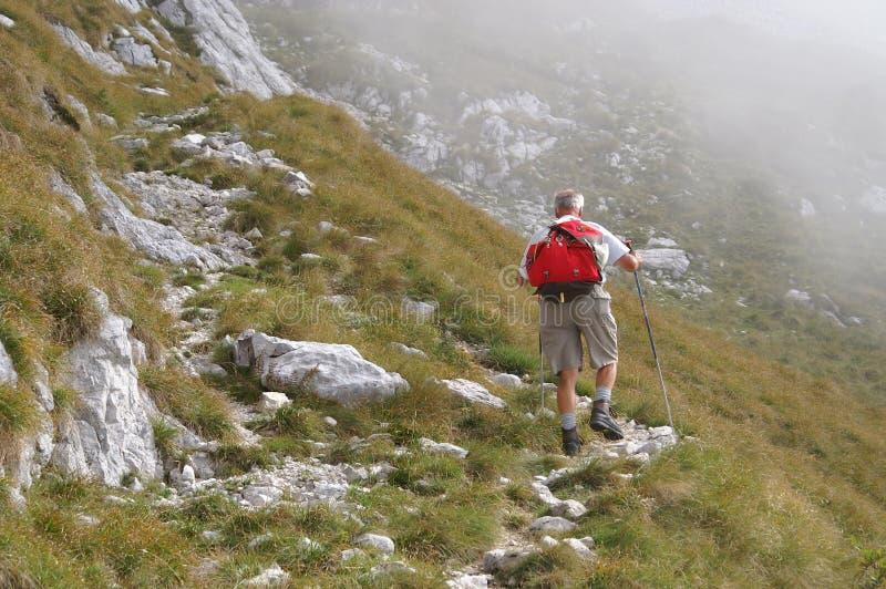 Older man walking uphill royalty free stock photo