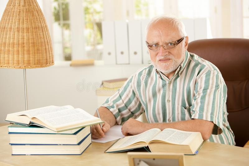 Older man working at his study stock images