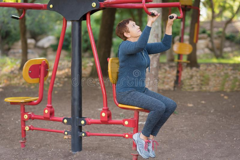 Older man working out on the sports public equipment in the outdoor gym. stock photos