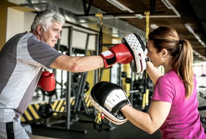 Older man boxing in gym. Senior man with personal trainer. stock photos