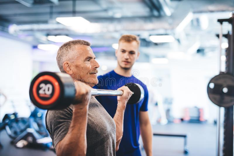 Older man lifting weights, supervised by gym assistant. royalty free stock photo