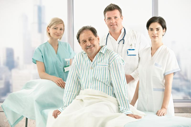 Older patient on bed with hospital crew. Older patient sitting on bed with hospital crew in background royalty free stock photos