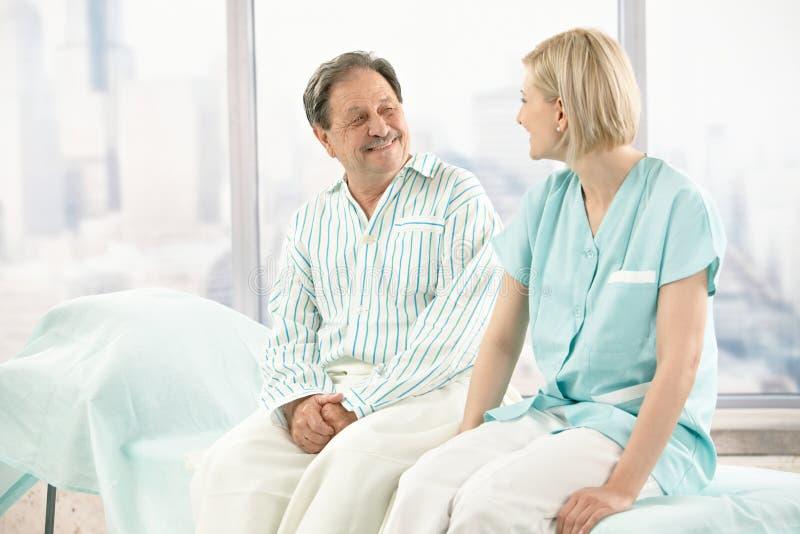 Older patient talking to nurse. Older patient wearing pyjama in hospital, talking to nurse, smiling royalty free stock photo