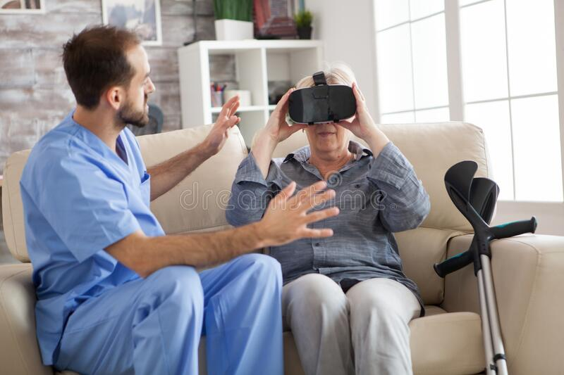 Older patient using virtual reality glasses in nursing home. To see her spine royalty free stock images