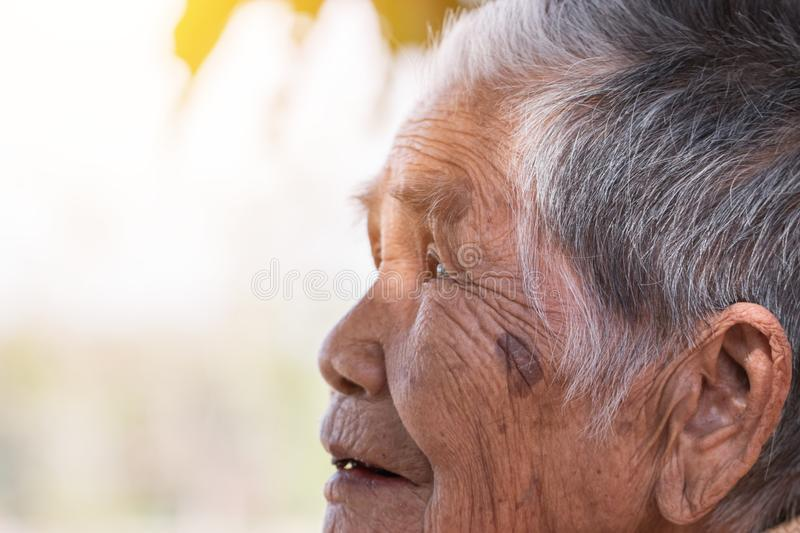 Older people for insurance concept: Portrait of Asian elder woman sitting alone with her black tooth at outdoor in sunny day royalty free stock images
