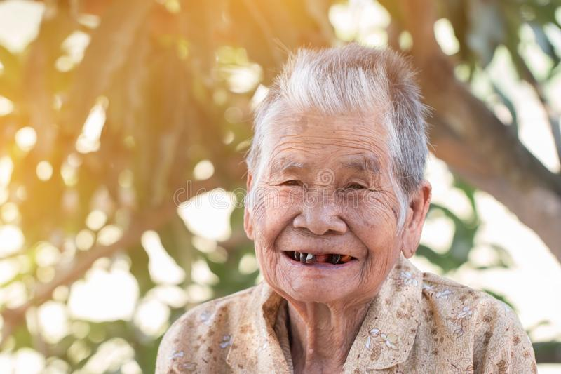 Older people for insurance concept : Portrait of Asian elder woman is smiling with her black tooth with happy at outdoor in sunny stock photo