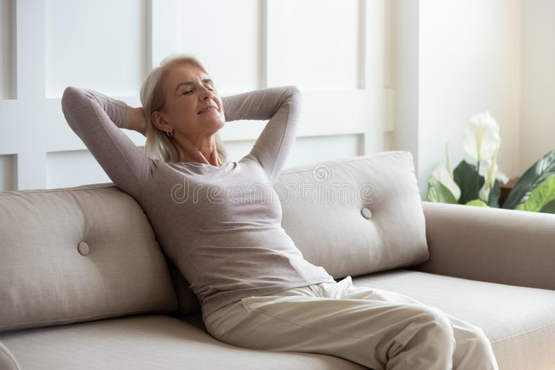 Older 50s female resting seated on couch with closed eyes. Older serene tranquil 50s female resting seated on sofa in living room, woman closed eyes put hands royalty free stock photos