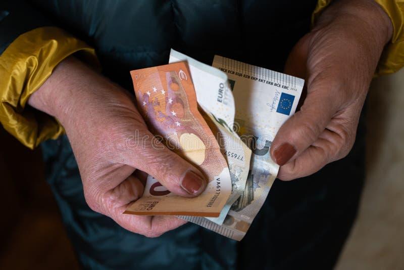 Older senior woman holds EURO banknotes - Eastern European salary pension stock photography
